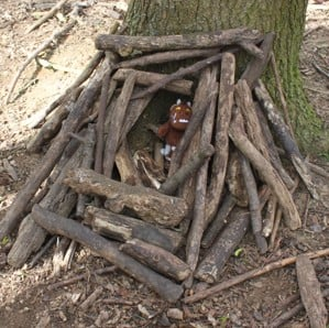 wooden house made of sticks in a wooded area for a toy Gruffalo
