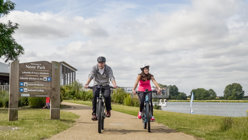 two cyclists riding by the lake in Nene Park