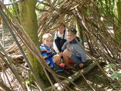three children in a shelter made from sticks in a wood