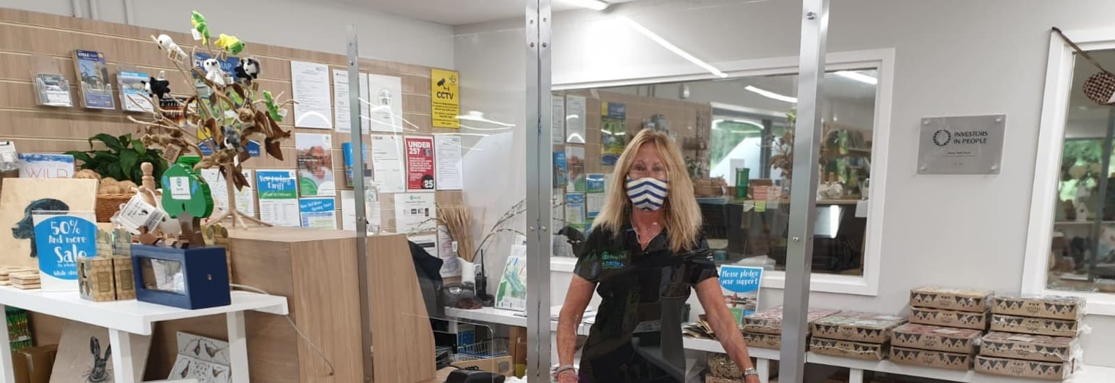 member of the visitor centre team behind the shop counter