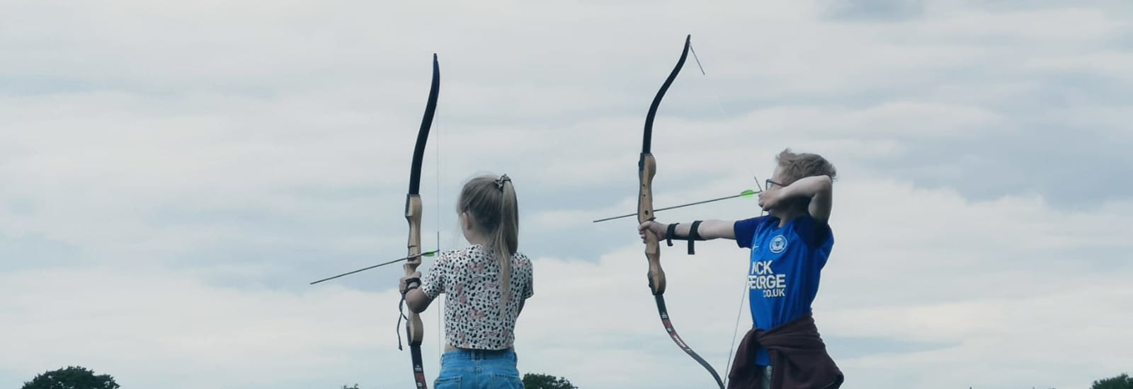 two children enjoying archery on a field