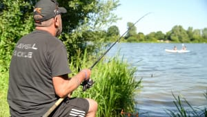 man fishing in a lake at nene park