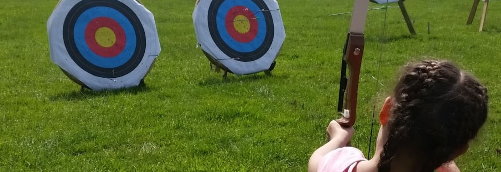girl playing archery in a park